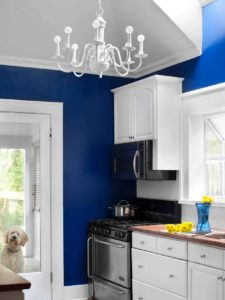 blue kitchen with white backsplash and chandelier